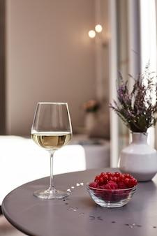 Blumenstrauß in einer vase, ein glas weißwein und frische himbeeren auf einem tisch auf der terrasse