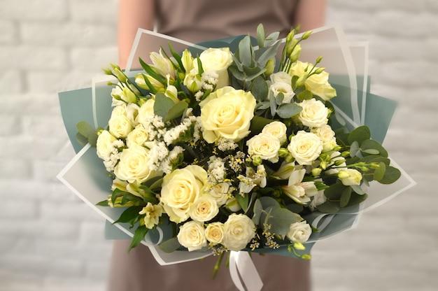 Blumenstrauß in frauenhänden. frau mit blumen für einen katalog.