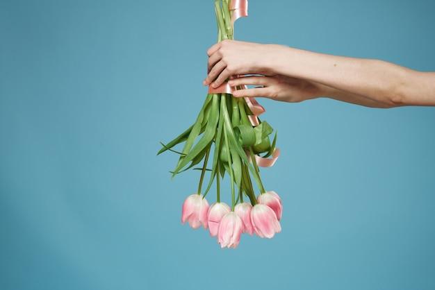 Blumenstrauß in frauenhänden mit blauem hintergrund des geschenkfeiertags valentinstag