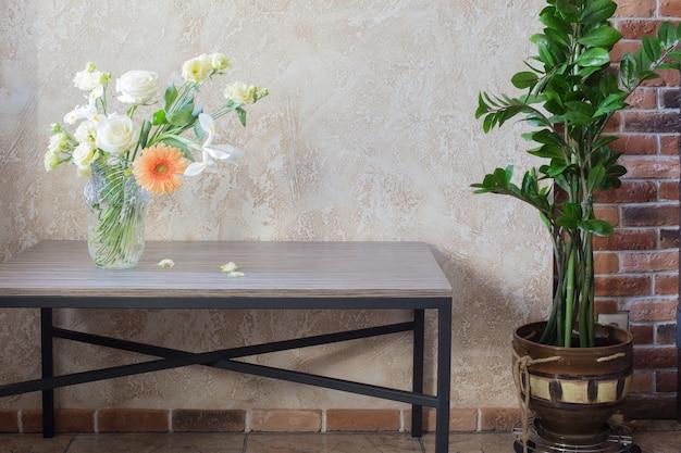 Blumenstrauß in glasvase auf dem tisch in der hintergrundwand