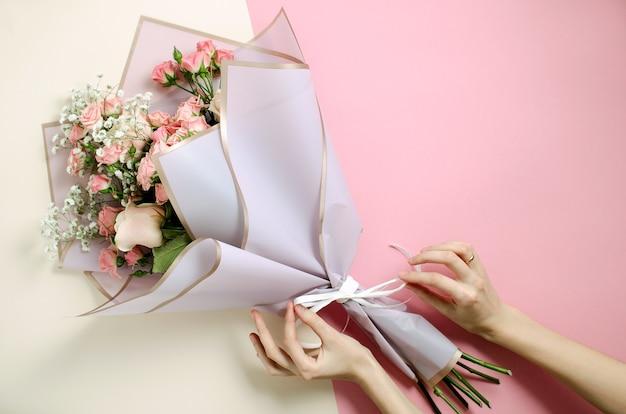 Blumenstrauß in rosa und nacktem hintergrund. draufsicht auf frau verziert einen blumenstrauß