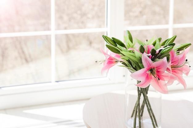 Blumenstrauß künstlicher blumen in einer glasvase auf einem weißen tisch vor einem großen fenster.