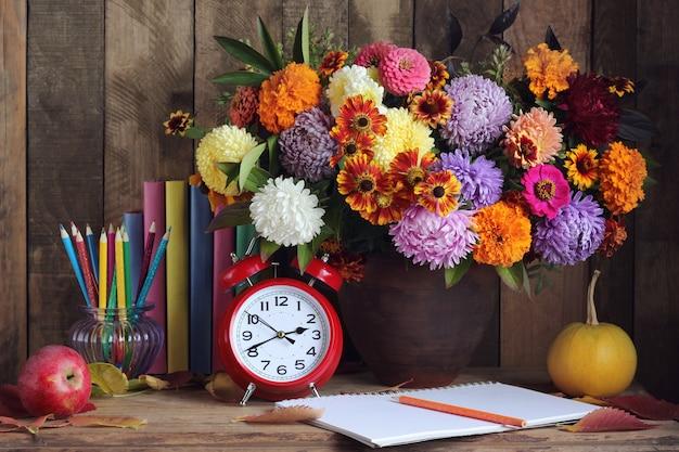 Blumenstrauß, kürbise, bleistifte, apfel, bücher und uhr auf dem tisch. stillleben. zurück zur schule. lehrertag. 1. september.