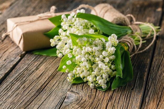 Blumenstrauß maiglöckchen auf natürlichem holzhintergrund