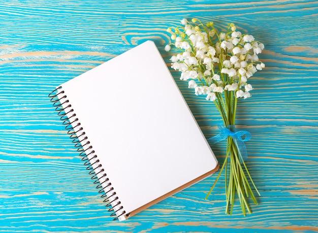 Blumenstrauß maiglöckchen und leeres notizbuch aus papier auf blauem rustikalem tisch von oben, draufsicht, platz für text, flache lage.