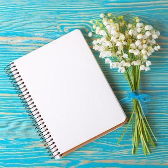 Blumenstrauß maiglöckchen und leeres notizbuch aus papier auf blauem rustikalem tisch