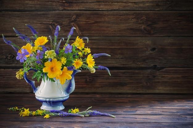 Blumenstrauß mit blauen und gelben blumen in der teekanne auf holztisch