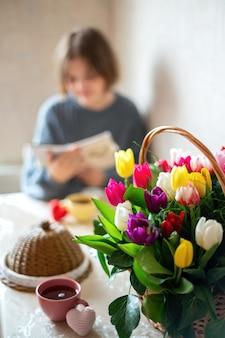 Blumenstrauß mit einem mädchen, das auf den tisch schreibt. küche