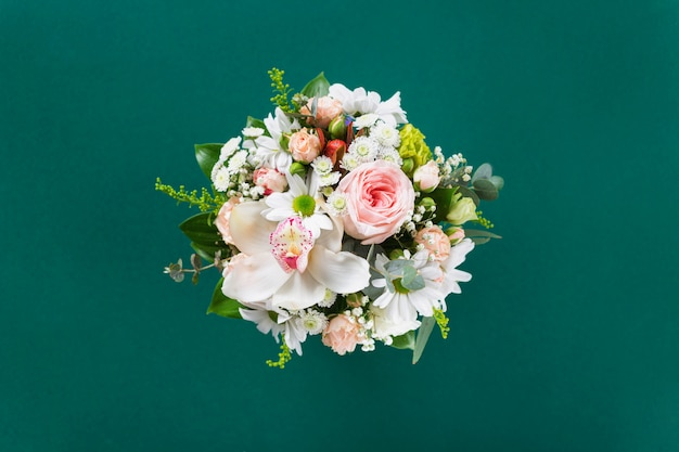 Blumenstrauß mit geschenk auf grünem hintergrund flache lage, draufsicht. valentinstag, liebeskonzept