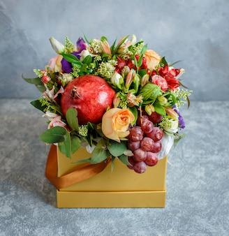 Blumenstrauß mit granatapfel, traube in gelber quadratischer schachtel