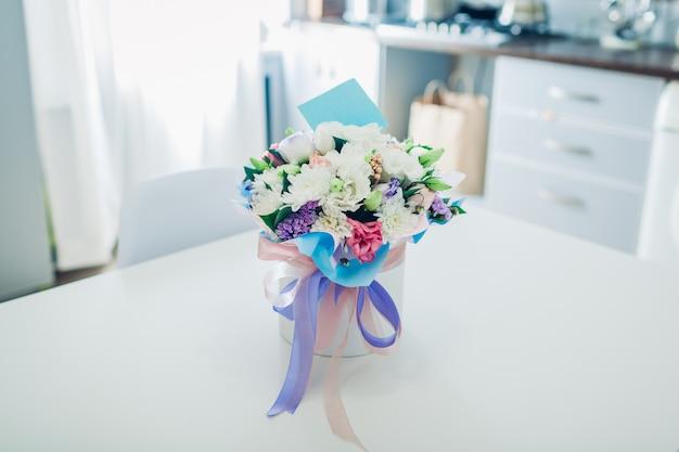 Blumenstrauß mit karte in geschenkbox links auf küche. überraschung für die frau. geschenk für den urlaub