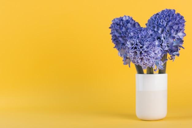 Blumenstrauß mit lila hyazinthen frühlingsblumen in einer vase auf gelbem kopierraum