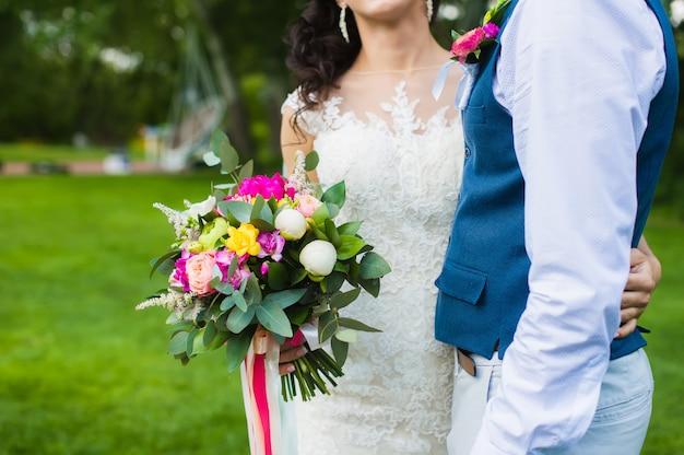 Blumenstrauß mit pfingstrosen und rosen in den händen der braut