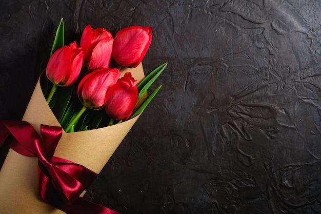 Blumenstrauß mit schleifenknotenband der roten tulpenblumen auf strukturierter schwarzer oberfläche, kopierraum der draufsicht