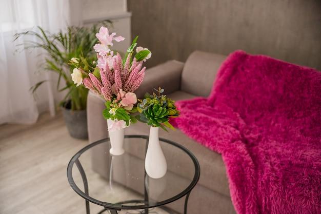 Blumenstrauß mit schönen künstlichen und saftigen kakteen der orange, lila blumen auf glastisch und palme und sofa in der wand. wohnzimmer interieur.