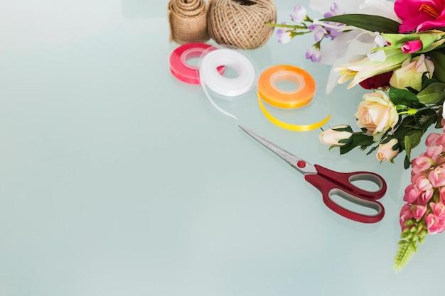 Blumenstrauß mit schreibwaren auf schreibtisch