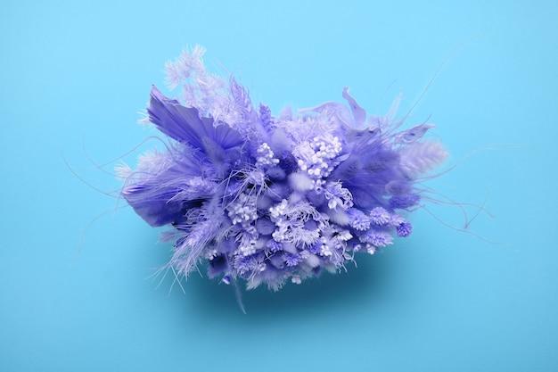 Blumenstrauß mit verschiedenfarbigen getrockneten wildblumen auf blauem tisch draufsicht