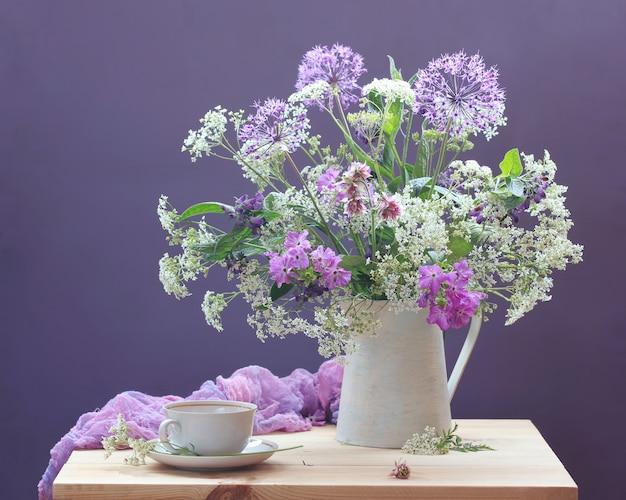 Blumenstrauß. stillleben mit garten und wilden blumen in einem krug und in einem teepaar auf einer tabelle