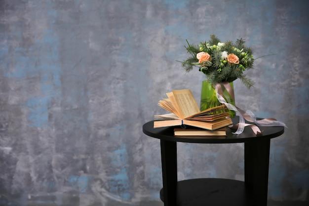 Blumenstrauß und bücher auf tisch gegen graue wand