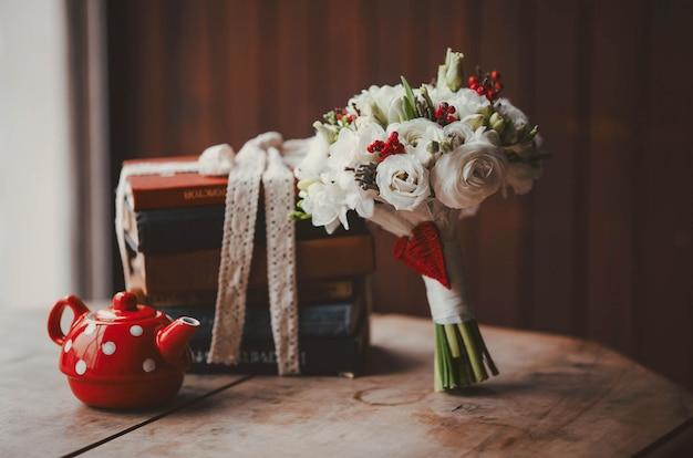 Blumenstrauß und eine rote teekanne
