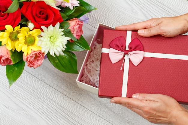 Blumenstrauß und frauenhände mit geschenkbox auf den grauen holzbrettern