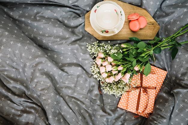 Blumenstrauß und geschenke nahe cup und nachtisch