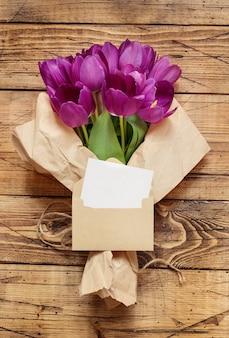 Blumenstrauß und leere karte auf hölzerner tischoberansicht