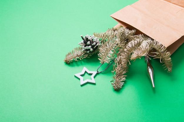 Blumenstrauß verziert mit tannenzapfen und weihnachtsspielzeug, grüner hintergrundkopierraum