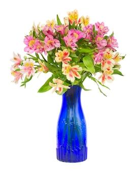 Blumenstrauß von alstroemeria-blumen im blauen glas lokalisiert auf weißem hintergrund