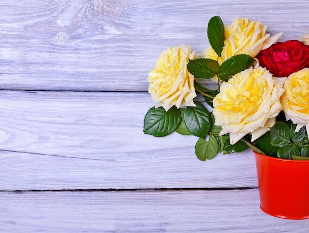 Blumenstrauß von blühenden rosen in einem orange eimer