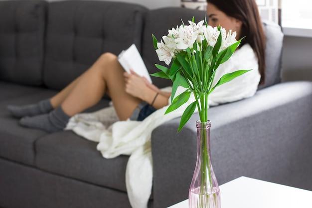 Blumenstrauß von blumen alstroemeria in der vase auf dem hintergrund des lesens der jungen frau, rest zu hause