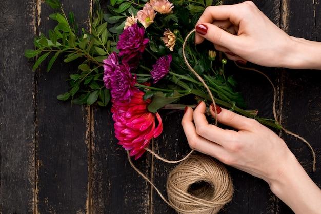 Blumenstrauß von blumen in der weiblichen hand auf einem schwarzen holztisch