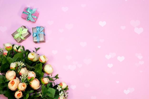 Blumenstrauß von blumen und von geschenkboxen auf rosa hintergrund mit herzen beleuchtet.