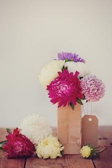 Blumenstrauß von bunten astern in der papiertüte. herbst. getöntes bild