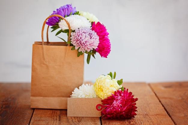 Blumenstrauß von bunten astern in der papiertüte mit leerer grußkarte