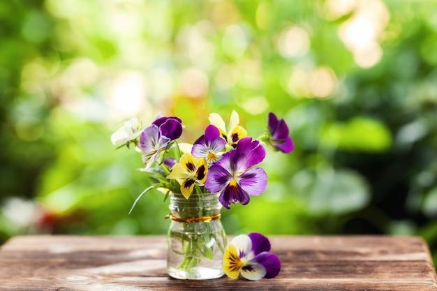 Blumenstrauß von bunten stiefmütterchen auf grünem naturhintergrund.