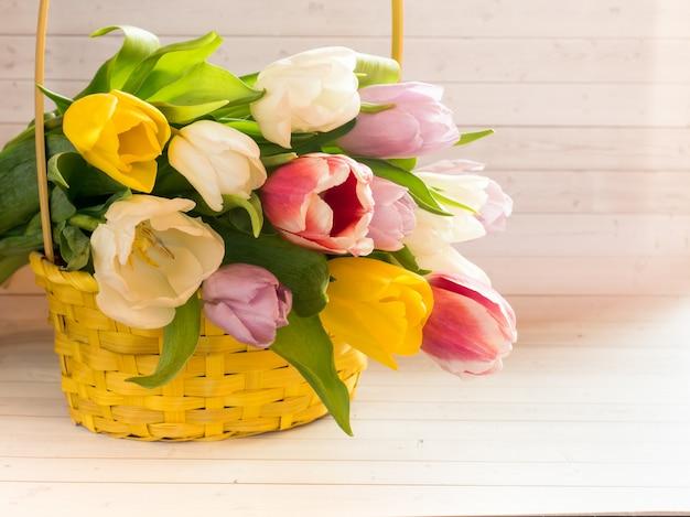 Blumenstrauß von bunten tulpen in einem gelben weidenkorb.