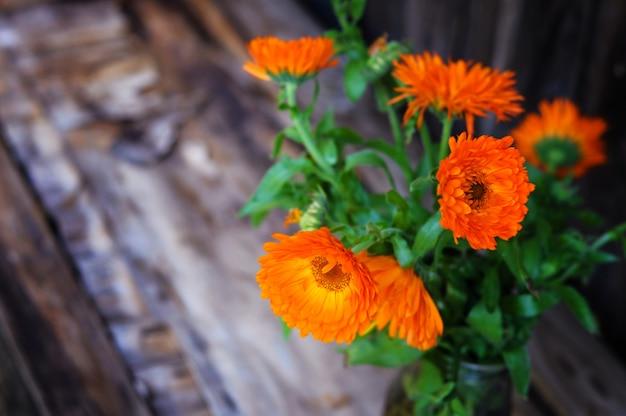 Blumenstrauß von calendulablumen auf der weinlese hölzern