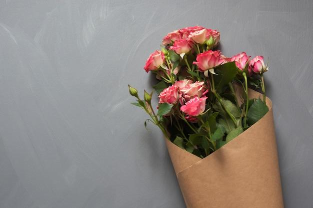 Blumenstrauß von den rosa buschrosen eingewickelt im kraftpapier auf grau