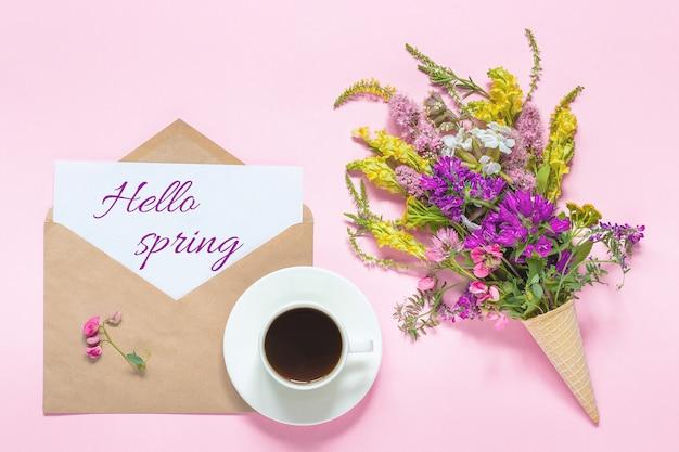 Blumenstrauß von farbigen blumen im waffelkegel, im tasse kaffee und im umschlag mit kartentext hallo frühling auf rosa wand
