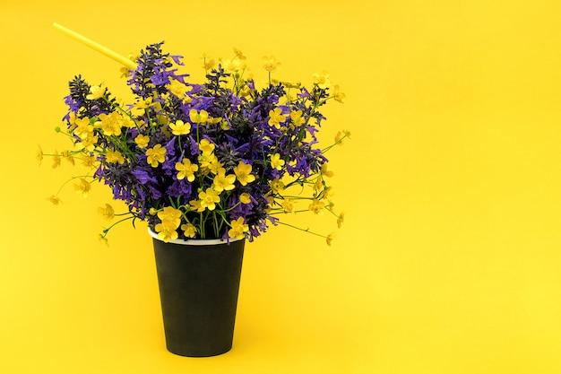 Blumenstrauß von farbigen blumen in der schwarzen papierkaffeetasse mit cocktailstroh auf gelb