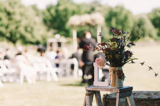 Blumenstrauß von feldblumen steht auf dem kleinen stuhl