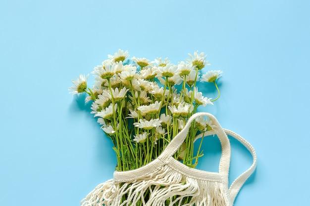 Blumenstrauß von feldgänseblümchen in wiederverwendbarer einkaufs-eco maschentasche auf blauem hintergrund