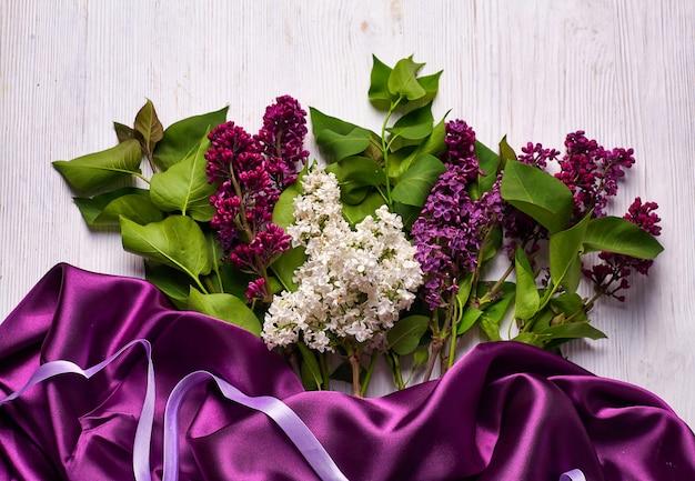 Blumenstrauß von fliederblumen und lila vorhängen auf weißem hintergrund. speicherplatz kopieren.