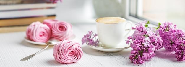 Blumenstrauß von fliedern, von tasse kaffee, von selbst gemachtem eibisch und von stapel büchern auf fensterbrett romantischer frühlingsmorgen.