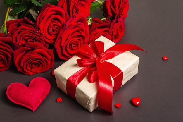 Blumenstrauß von frischen burgunderrosen, geschenk und festlichen herzen auf einem schwarzen steinbetonhintergrund. duftende rote blumen, geschenkkonzept für valentinstag, hochzeit oder geburtstag, flache lage