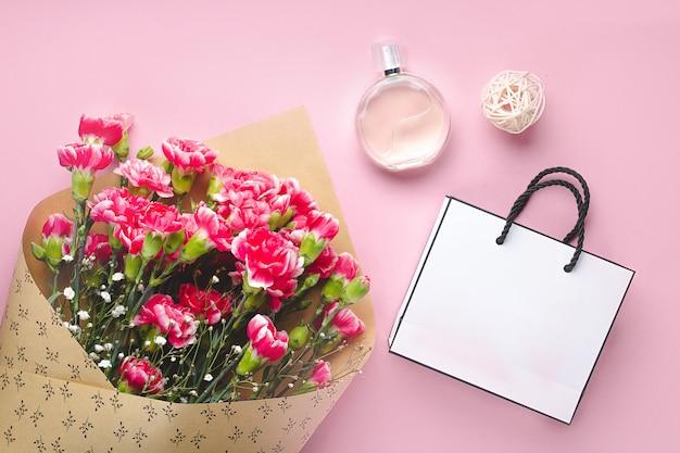 Blumenstrauß von frischen gartennelken, von flasche frauenparfüm und von weißen geschenkpapiertüte auf rosa hintergrund. empfangen von geschenken, geschenken und blumen von geliebten menschen