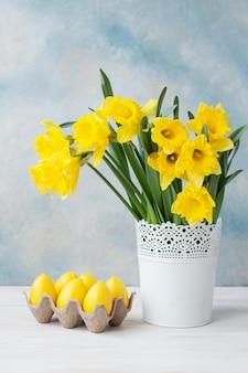 Blumenstrauß von frischen gelben narzissen im vase und in den dekorativen eiern auf himmelblauhintergrund