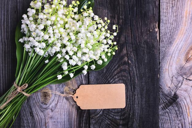 Blumenstrauß von frischen maiglöckchen auf einer grauen holzoberfläche