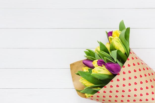 Blumenstrauß von frühlingsblumen eingewickelt im papier mit herzen auf weißem holztisch.